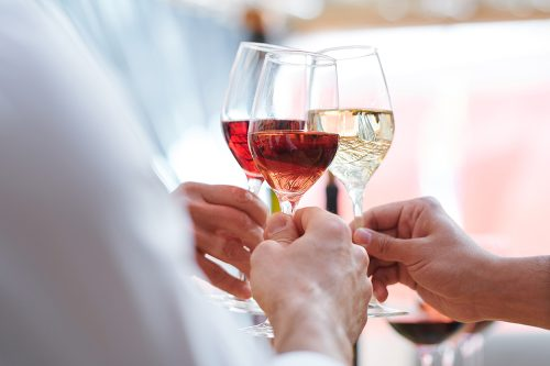 Human hands holding wineglasses with champagne, cabernet and brandy