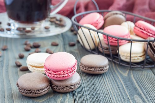 Different kinds of colorful french dessert macaron with different fillings on table, served with coffee, horizontal